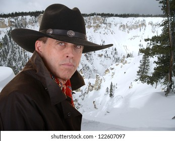 Handsome cowboy wearing a red scarf against a snowy winter canyon