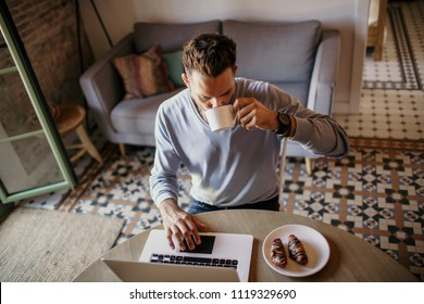 Handsome coworker man working at living room at home. Man sitting at wooden table using laptop and mobile phone. Blurred background