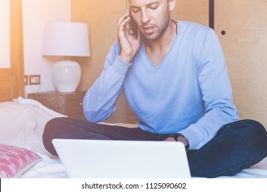 Handsome coworker man working at living room at home. Man sitting at bed using laptop and mobile phone. Blurred background.Flares