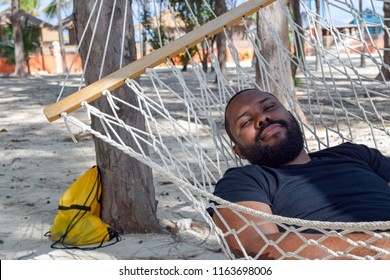 Handsome/ Cute young smiling black man/ male mid 40s with beard and mustache lying in hammock under tree in shade on tropical Caribbean sand beach in summer on vacation holiday weekend looking content