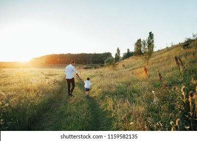 Handsome dad with his little cute son are having fun and playing on green grassy lawn. Happy family concept. Beauty nature scene with family outdoor lifestyle. family resting together. Fathers day