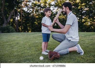 Handsome dad with his little cute sun are playing baseball on green grass lawn
