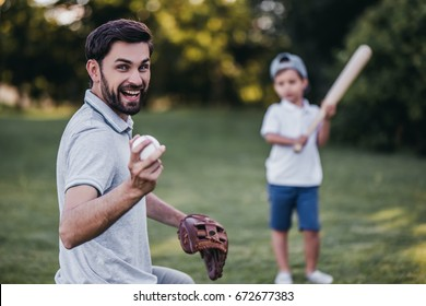 Handsome dad with his little cute sun are playing baseball on green grassy lawn