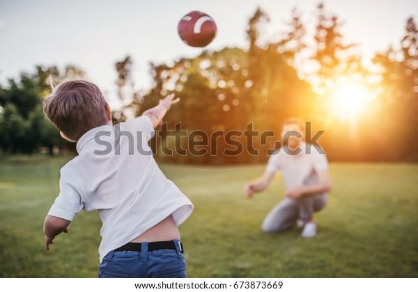 Un padre guapo con su pequeño sol lindo se está divirtiendo y jugando fútbol americano en el césped verde y verde