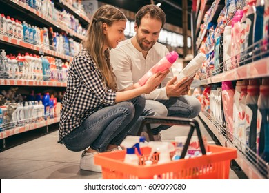Handsome dad and his pretty daughter are choosing household objects while doing shopping in supermarket