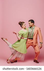 handsome dancer hugging girl while dancing boogie-woogie on pink background
