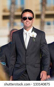 A handsome dark-haired groom outdoors in the sunlight