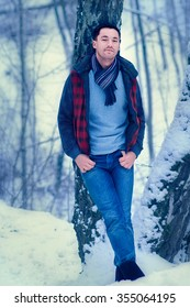 Handsome dark-haired young man against a snow-covered park background. Vertical image with selective focus and toning