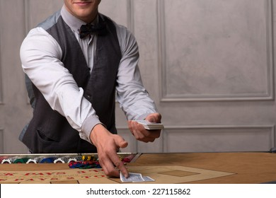 Handsome  dealer  laying out cards on  table with  red blue and white chips in piles in casino