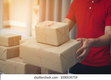 Handsome Deliver Male in red Uniform Postal Delivery Courier man in front of Cargo Van Delivering Package.Fast and free Delivery TRANSPORT .Online Shopping and Express Delivery theme.