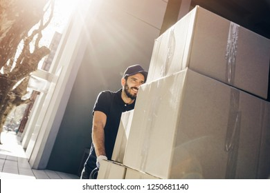 Handsome delivery man or mover pushing a stack of boxes on a dolly, outdoors.
