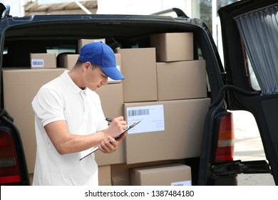 Handsome delivery man near car with parcels outdoors