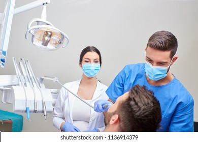 A handsome dentist and a beautiful assistant giving dental treatment to the patient.