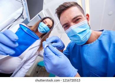 A handsome dentist and a beautiful assistant at a treatment, from the perspective of the patient.