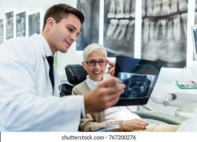 Handsome dentist looking at x-ray image of his senior woman patient.