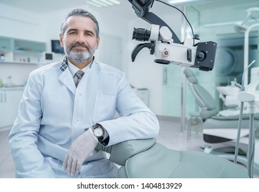 Handsome dentist sitting in chair, posing, looking at camera. Bearded mature man wearing in white coat working in private dentistry clinic with modern equipment, professional microscope.