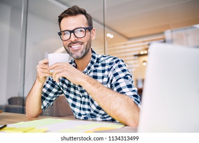 Handsome designer drinking coffee working from home office