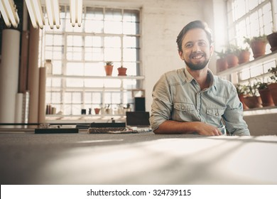 Handsome designer entrepreneur smiling at the camera while relaxing in his studio with gentle sun flare coming in through the window