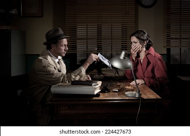 Handsome detective at office desk showing a picture to a young woman, film noir scene.