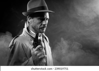 Handsome detective in trench coat holding a gun in the dark, film noir