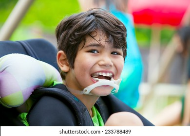 Handsome disabled eight year old biracial boy smiling and relaxing in wheelchair