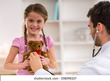 Handsome Doctor examining little girl with stethoscope