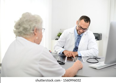 handsome doctor giving medical consultation diagnostic  to elderly senior woman in hospital office