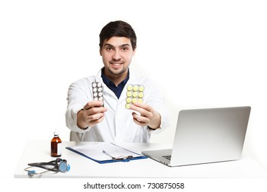 handsome doctor man in his office at the desk, shows tablets for colds and coughs