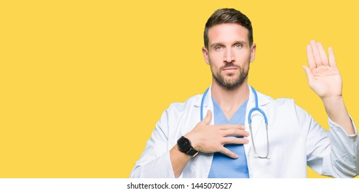 Handsome doctor man wearing medical uniform over isolated background Swearing with hand on chest and open palm, making a loyalty promise oath