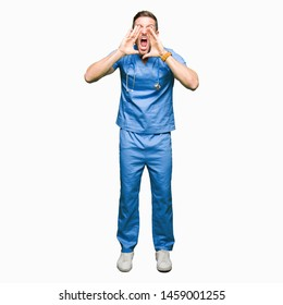 Handsome doctor man wearing medical uniform over isolated background Shouting angry out loud with hands over mouth