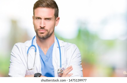 Handsome doctor man wearing medical uniform over isolated background skeptic and nervous, disapproving expression on face with crossed arms. Negative person.