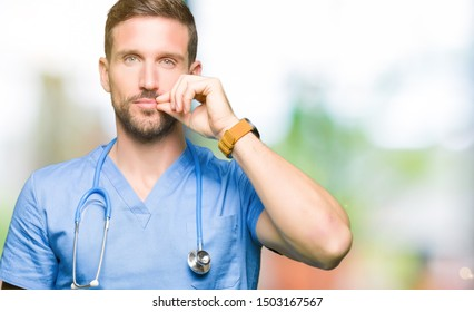 Handsome doctor man wearing medical uniform over isolated background mouth and lips shut as zip with fingers. Secret and silent, taboo talking