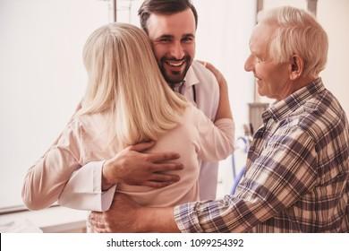 Médico bonito está encontrando um velho casal de pacientes, abraçando mulher e sorrindo