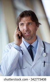 handsome doctor speaking on cellphone at modern hospital indoors