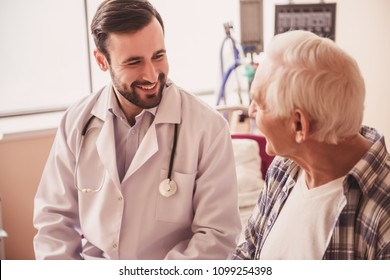 Handsome doctor is talking with an old man and smiling while sitting in hospital ward