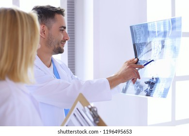 Handsome doctor is talking with young female doctor and making n