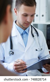 Handsome doctor is talking with young female patient and making notes while sitting in his office.