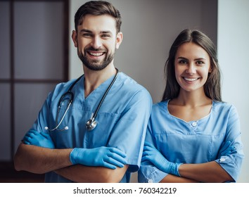 Handsome doctor veterinarian and his attractive assistant at vet clinic. Standing with hands crossed, smiling and looking at camera.