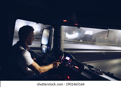 A handsome driver at the wheel of a truck is driving his goods at night.