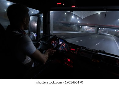 Handsome driver at the wheel of a truck at night.