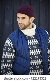 Handsome dude in body warmer and sweater, looking away