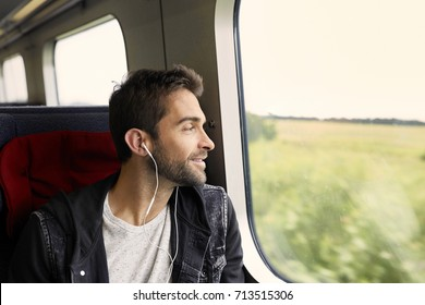 Handsome dude on train listening to music