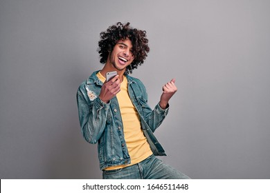 Handsome eastern excited man dancing with smartphone in hand on isolated gray background. Joyful student with phone