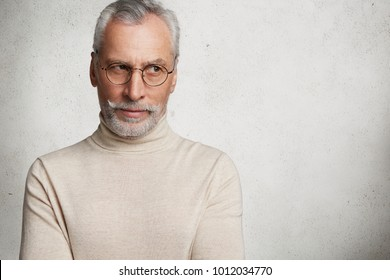 Handsome elderly male pensioner remembers all his life, positive and negative moments, has thoughtful serious expression, dressed in casual turtleneck sweater, isolated over white background