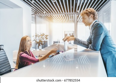 Handsome elegant caucasian man in formal suit is leaning on white table top of reception and giving his plastic card to beautiful female receptionist for payment, bright office space or hotel around