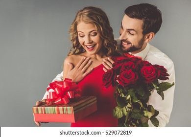 Handsome elegant guy in classic shirt with red bow tie is giving roses and gift box to his beautiful girlfriend and smiling