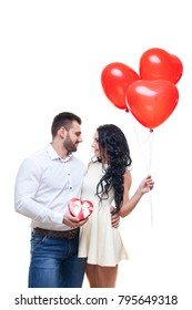 Handsome elegant guy is presenting a heart shaped gift and balloons to his beautiful girlfriend and smiling, valentines day theme. isolated on white background