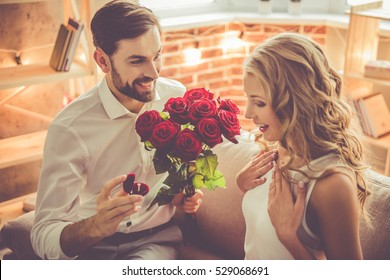 Handsome elegant guy is proposing to his beautiful girlfriend, giving her roses and smiling while they having a romantic date at home