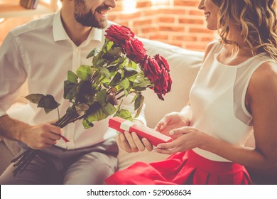 Handsome elegant guy is smiling, giving his beautiful girlfriend roses and a present while they having a romantic date at home