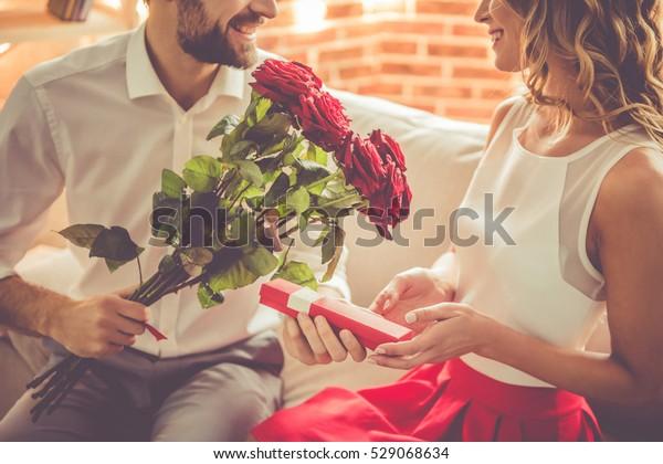 イケメンなエレガントな男性は笑顔で、美しい彼女のバラとプレゼントを贈りながら、家でロマンチックなデートをする